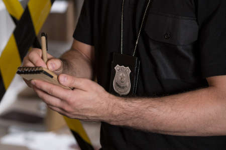 police tape: Close-up of policeman with badge taking notes at the crime scene Stock Photo