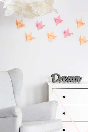 wall decor: Light home interior with dresser, armchair and origami wall decor