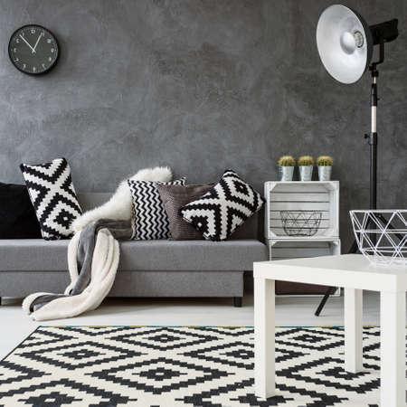 ソファ、イス、小さな灰色のリビング ルーム テーブルを白、黒と白のカーペットを新しいパターン