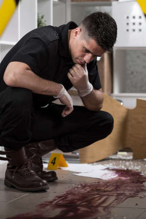 crouches: Thoughtful policeman crouches over a stain of blood inside the office