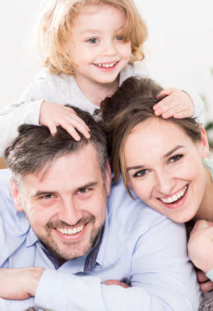 cropped shot: Cropped shot of a cute girl keeping hands on her parents heads