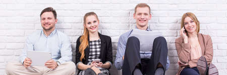 working team: Smiled and relaxed team members are sitting on floor an leaning on brick wall Stock Photo