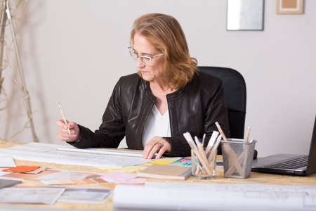 business plan: Mature female architect working on plans at desk