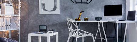 Vue panoramique d'un bureau à domicile gris avec chaise en cristal, bureau, ordinateur et revêtement mural décoratif
