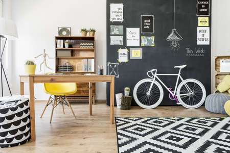 decorated bike: Shot of a creative studio with a desk, bike and chalkboard wall decorated with posters
