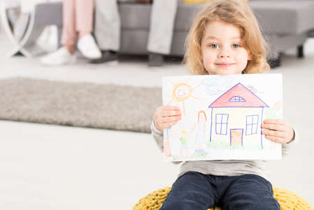youngsters: Shot of a little girl sitting on the pillow and holding a picture in her hands