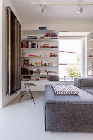 minimalist interior: Shot of a white living room with a big window and a grey sofa