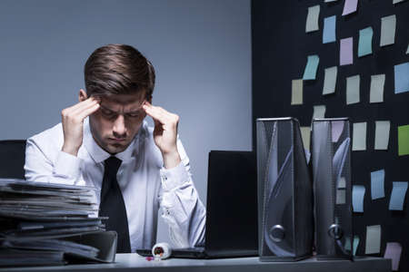 overworking: Shot of a businessman staying late in his office and having a headache