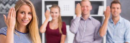"""personas comunicandose: Vista panorámica de una gente joven que muestra la palabra """"dar la bienvenida"""" usando el lenguaje de signos"""