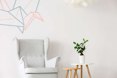 Light home interior with armchair, side table and washi tape wall decor Stock Photo