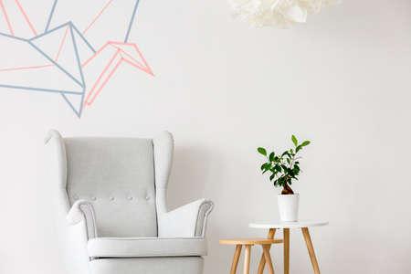 Luz interior de una casa con sillón, mesa auxiliar y decoración de la pared de cinta washi Foto de archivo