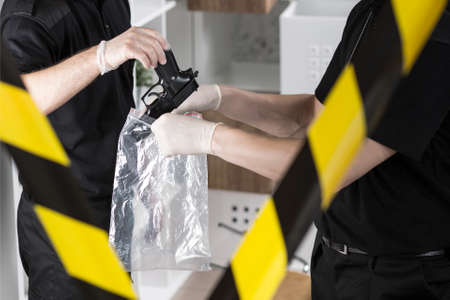 police tape: Policeman put a gun in a plastic bag held by another investigator