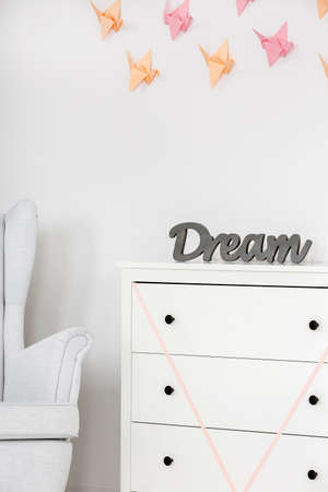 wall decor: White room with new dresser, armchair and origami wall decor Stock Photo