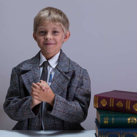 Smart little boy standing at the desk with encyclopedias Stock Photo