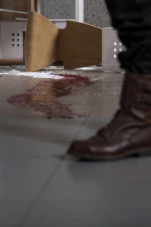 Vue du mobilier de bureau renversé et des traces de sang examinées par un policier Banque d'images - 63275749