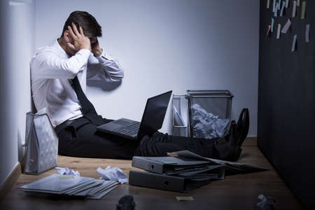 Shot of an overwhelmed businessman sitting on a floor in his messy office and holding his head