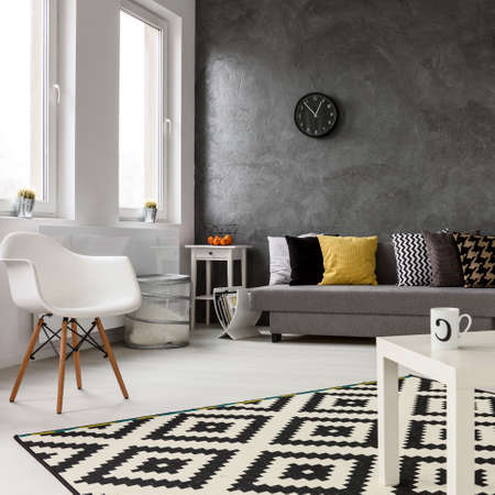 Spacious lounge with modern stylish design with grey walls and white wooden parquet. On the floor pattern carpet
