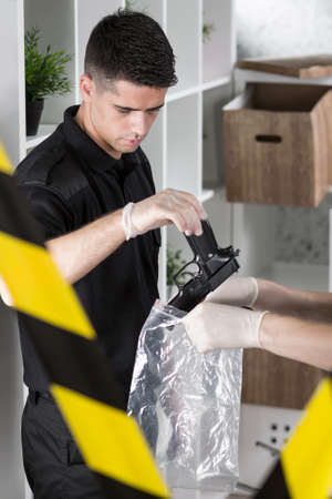evidence bag: View of policeman putting a gun in a plastic bag held by another investigator Stock Photo