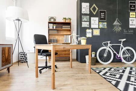 designed: Shot of a wooden desk in a creatively designed studio with a chalkboard wall