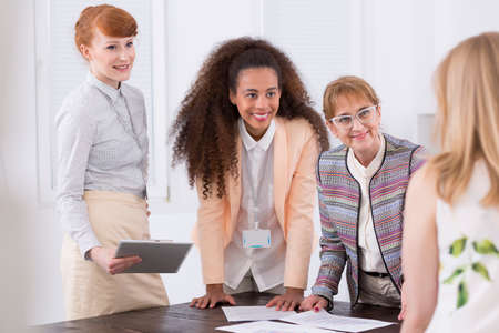 Deliberation of four businesswomen standing at one common desk Stock Photo