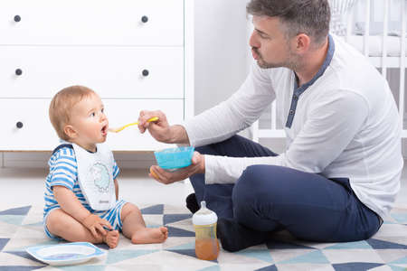 paternity: Shot of a dad sitting on a floor and feeding his little baby Stock Photo