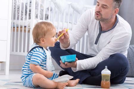 paternity: Shot of a dad feeding his baby in a nursery room