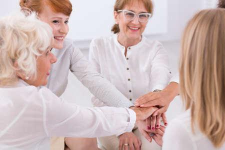 Glimlachte en tevreden vrouwen in witte kleren maken van een cheer Stockfoto