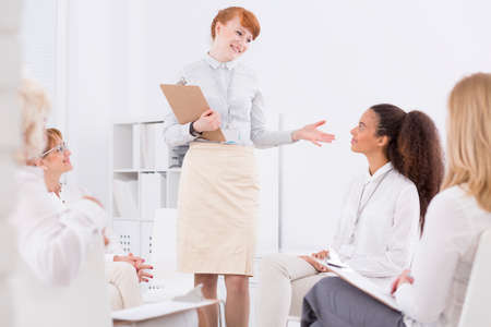 patrimony: Team leader commending the woman in room with other employees