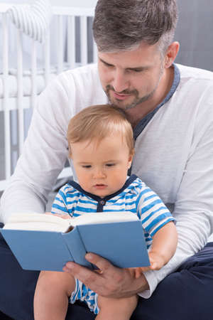 Shot of a men holding a baby and reading a book to him