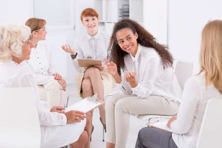 space   area: White clothed businesswomen sitting together in an open space area and talking
