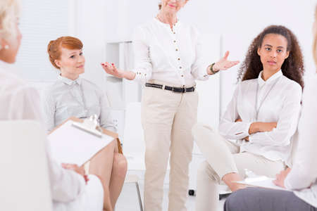 brain storming: Various generations of women sitting together at wark and talking about the campaign Stock Photo