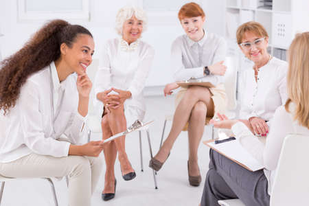 association: Association of white dressed women sitting together in circle