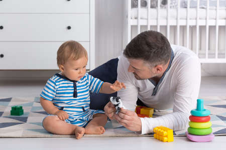 attachments: Shot of a little baby sitting on a floor and playing with his dad Stock Photo