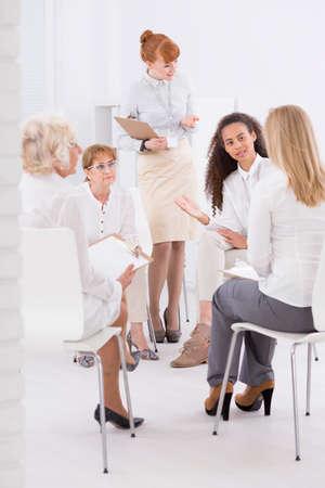 elegantly: Meeting of elegantly dressed women with the team leader
