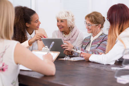 one on one meeting: Meeting of businesswomen sitting at one desk in the work office Stock Photo