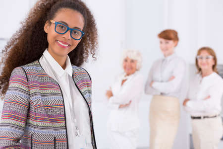 clothed: Three white clothed woman standing behind the smiled woman in glasses Stock Photo
