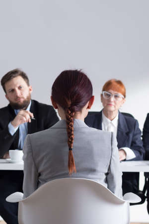 recruiters: Young woman sitting in front of recruiters during job interview Stock Photo