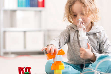 respiratory: Cropped shot of a small girl treated with a nebulizer while playing with her toys Stock Photo