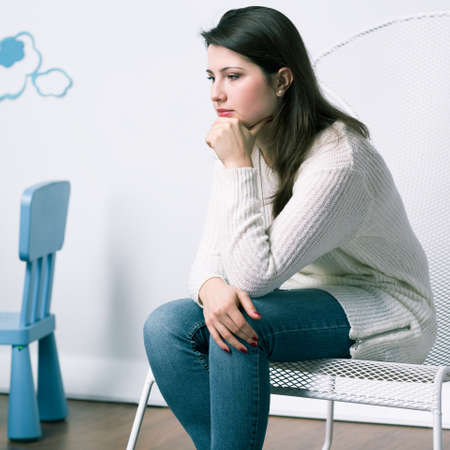 Sad woman sitting in baby room, missing her child