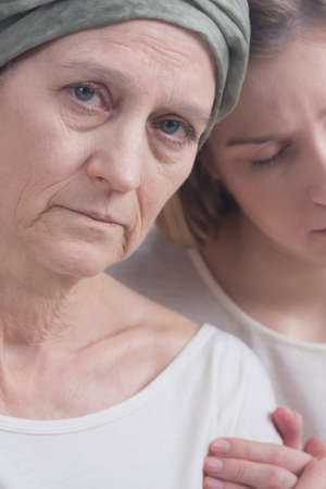 weak: Middle-aged weak woman sick with cancer embraced by daughter Stock Photo
