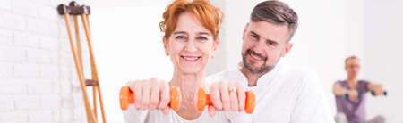 patient care: Shot of a handsome physiotherapist and his female patient exercising with dumbbells Stock Photo