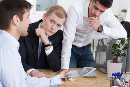 pitched: Conversation of three elegant men at the office, pitched on a desk