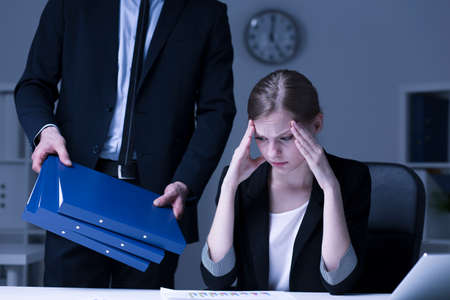 at her desk: Shot of a stressed young worker sitting at her desk