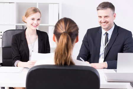 recruiters: Shot of two smiling recruiters asking questions to a young applicant