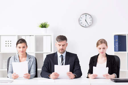 recruiters: Shot of a team of professional recruiters reading CVs