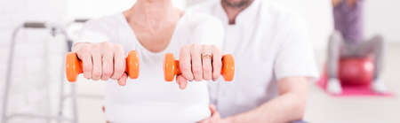 patient care: Cropped shot of a woman holding dumbbells