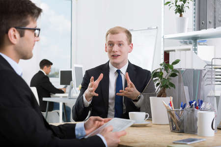 workmate: Elegant man talking to his workmate with the gesticulation Stock Photo