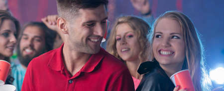 celeb: Young couple looking at each other with other people at the background Stock Photo