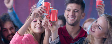 smiled: Group of smiled students dancing with drinks in their hands Stock Photo