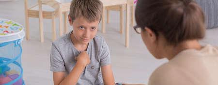 profesor alumno: Un niño sentado en el suelo delante de su terapeuta Foto de archivo